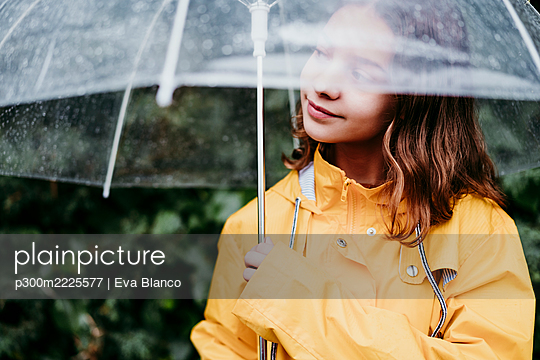 Girl in raincoat looking away while standing under umbrella outdoors - p300m2225577 by Eva Blanco