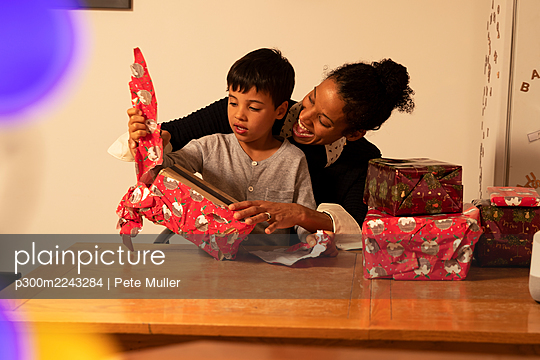 Cheerful mother with son unwrapping Christmas presents on table at home - p300m2243284 by Pete Muller