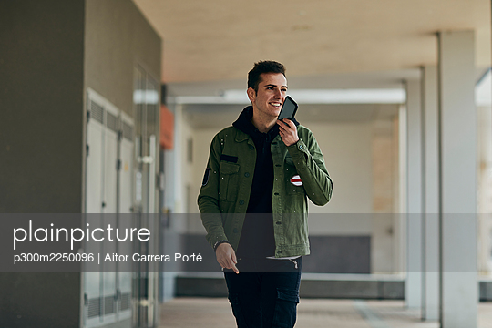 Handsome man holding mobile phone in front of face while looking away in arcade - p300m2250096 by Aitor Carrera Porté