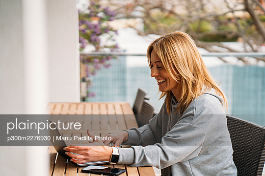 Smiling female professional using laptop in balcony at home - p300m2276930 by Manu Padilla Photo