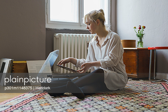 Full length of woman playing record while sitting at home - p301m1148375 by Halfdark