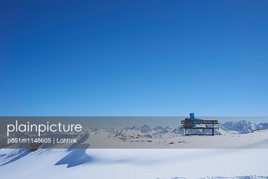 Frau auf einer Bank in Winterlandschaft - p851m1148605 von Lohfink