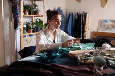 Calm seamstress woman sewing in home workshop - p1166m2218556 by Cavan Images