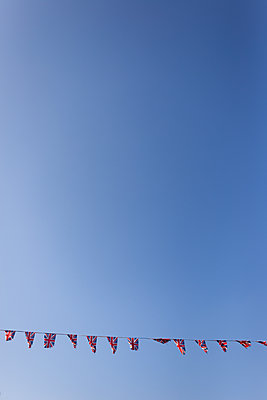 Union Jack buntings against blue sky - p1335m1586381 by Daniel Cullen
