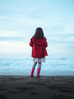 Little girl in red raincoat on the beach, rear view - p1522m2273352 by Almag