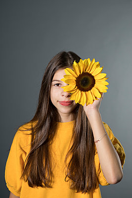 Portrait of smiling girl with sunflower in front of grey background - p300m2062457 von Petra Stockhausen