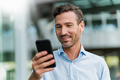 Smiling businessman with earphones and cell phone in the city - p300m2139779 von Daniel Ingold