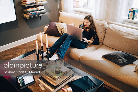 High angle view of girl using mobile phone and laptop while sitting on sofa - p426m1555911 by Maskot