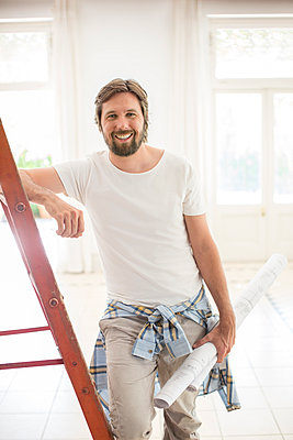 Man standing on ladder in living space - p1023m962422f by Sam Edwards