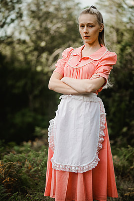 Young woman in pink dress and white apron - p1628m2211984 by Lorraine Fitch