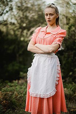 Junge Frau im rosa Kleid mit weißer Schürze - p1628m2211984 von Lorraine Fitch