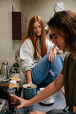 Teenage couple makes coffee in the kitchen - p1640m2242119 by Holly & John