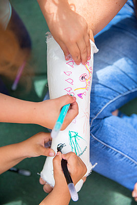 Little girls painting her mother's plaster arm - p300m1156835 by Enrique Ramos
