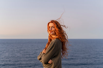 Portrait of redheaded young woman with windswept hair at the coast at sunset, Ibiza, Spain - p300m2159928 von VITTA GALLERY