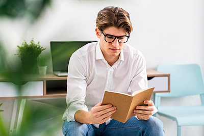 Young man wearing eyeglasses reading book in living room - p300m2265490 by Giorgio Fochesato