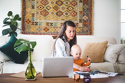 Busy female parent running business while taking daughter's care at home - p426m2117048 by Maskot