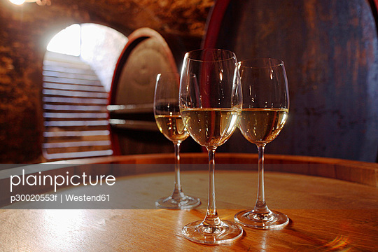 White wine in glasses on wine cask