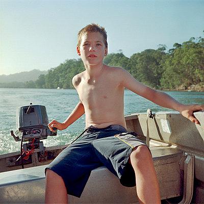 Boy steering boat - p1125m917365 by jonlove