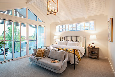 Home showcase interior bedroom with vaulted ceiling and patio - p1192m2047670 by Hero Images