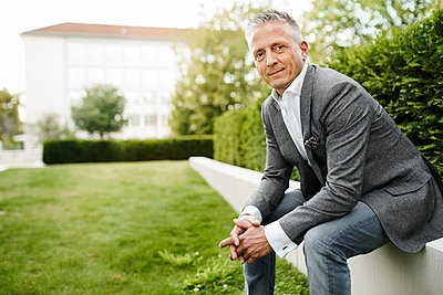 Male restaurateur sitting on retaining wall by plants - p300m2276434 by Sandro Jödicke