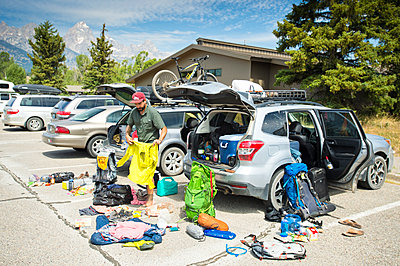 A backpacker prepares his gear before a hike. - p343m1184699 by Rob Hammer