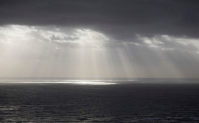 Sun Rays Reflected on Ocean Through Gray Clouds - p694m663704 by Maria K