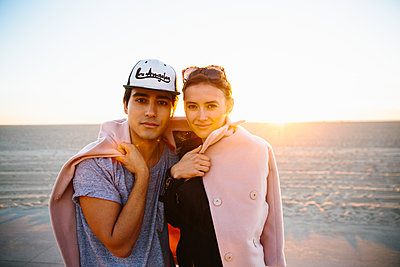 Portrait of young couple wrapped in overcoat on beach, Venice Beach, California, USA - p924m1135949f by Tanveer Badal
