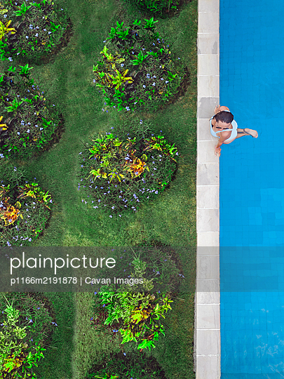 Aerial view of attractive woman floating over water at resort - p1166m2191878 by Cavan Images