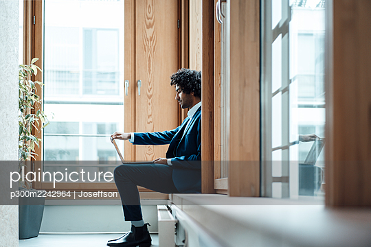 Young male entrepreneur using laptop while sitting against window at workplace - p300m2242964 by Joseffson