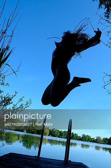 Jumping in the air by the lake - p427m2203627 by Ralf Mohr