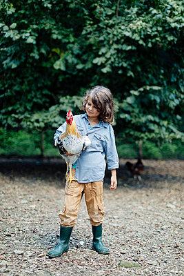 Boy holding chicken on an organic farm - p300m2144740 von Sofie Delauw