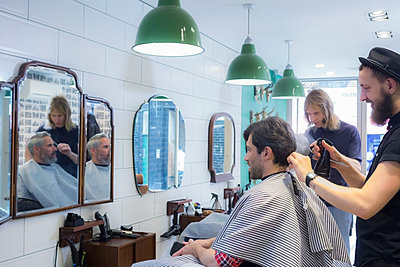 Hairdressers cutting customer's hair at barber shop - p300m2240012 by LOUIS CHRISTIAN