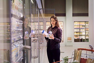 Woman holding juice boxes at refrigerated section in supermarket - p426m1451836 by Maskot