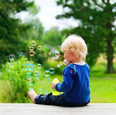 Boy blowing bubbles on porch - p42918039f by Henrik Weis