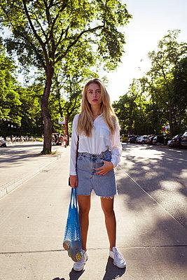 Nachdenkliche junge Frau mit Einkaufstasche - p432m1586263 von mia takahara