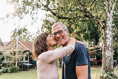 Reife Frau küsst Mann auf die Wange - p586m1178416 von Kniel Synnatzschke