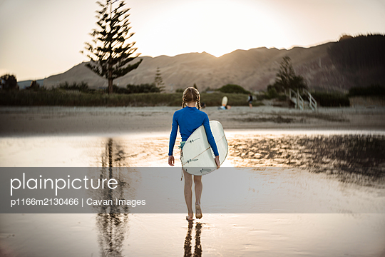 Preteen girl on beach at dusk carrying surfboard - p1166m2130466 by Cavan Images