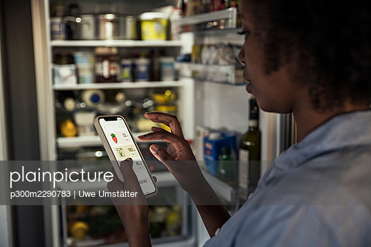 Woman counting food calories through smart phone by refrigerator at home - p300m2290783 by Uwe Umstätter