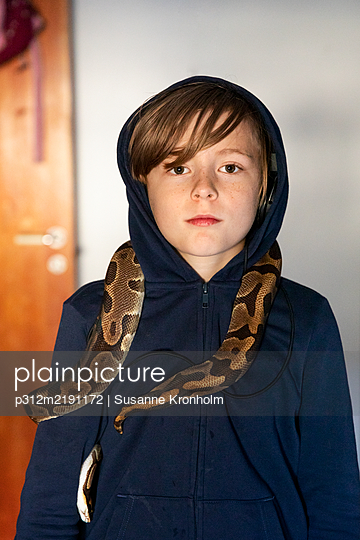 Boy with python on his shoulders - p312m2191172 by Susanne Kronholm