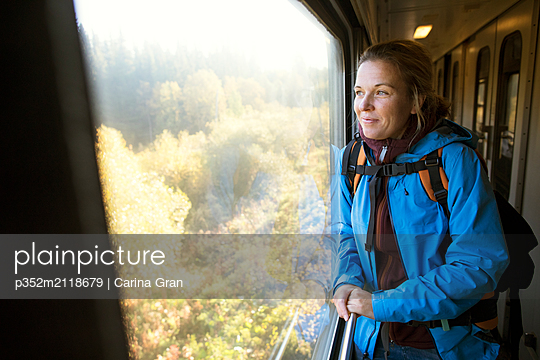 Woman looking through train window - p352m2118679 by Carina Gran