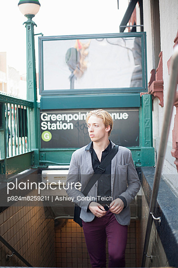 Young man emerging from subway station Brooklyn, New York City, USA - p924m825921f by Ashley Corbin-Teich