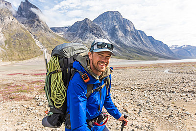 Smiling backpacker wearing rain jacket in mountain pass. - p1166m2261226 by Cavan Images