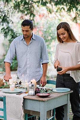 Couple preparing a romantic candelight meal outdoors - p300m2068801 by Alberto Bogo