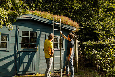 Father and son holding ladder in front of house - p300m2276963 by Gustafsson
