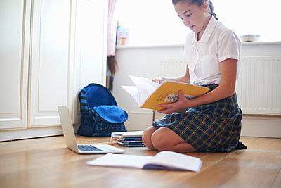 Teenage schoolgirl kneeling on floor looking at book - p429m1494572 by Peter Muller