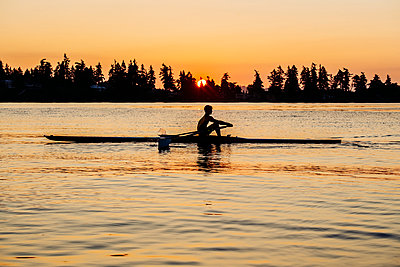 Silhouette of Caucasian man rowing at sunset - p555m1303402 by Pete Saloutos