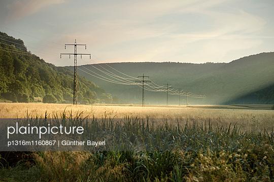 Landschaft mit Strommasten im Morgenlicht, Schelklingen, Biosphärengebiet Schwäbische Alb, Baden-Württemberg, Deutschland - p1316m1160867 von Günther Bayerl