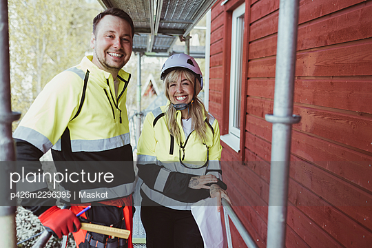 Cheerful male and female colleague standing together at scaffolding - p426m2296395 by Maskot