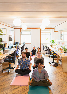 Serene creative business people meditating in office - p1023m2016629 by Tom Merton
