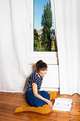 Junge Frau blättert in einem Buch, Stay at home durch Covid-19 - p1229m2181635 von noa-mar